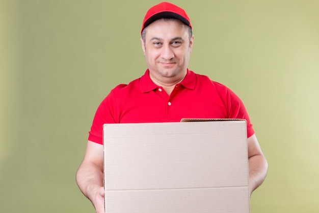 Entregador vestindo uniforme vermelho e boné segurando uma grande caixa de papelão, sorrindo amigavelmente com uma cara feliz em pé sobre um espaço verde isolado