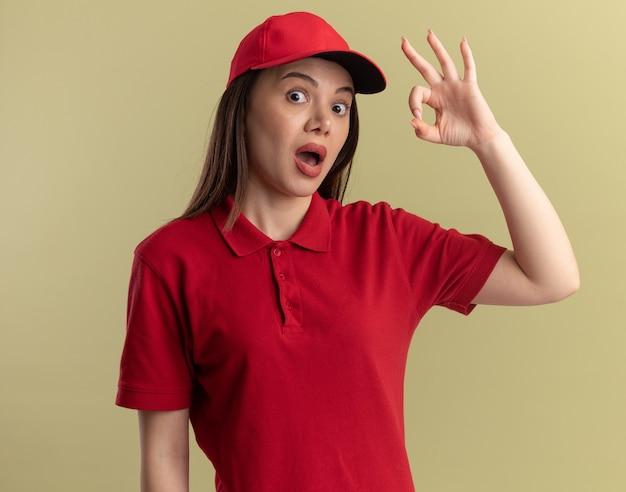 Entregadora bonita animada em gestos de uniforme, sinal de mão ok