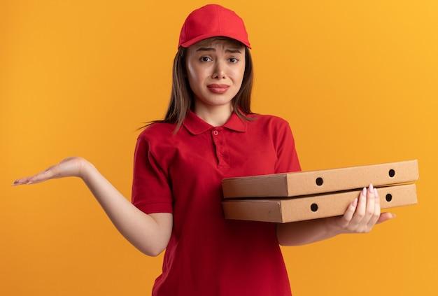 Entregadora bonita e triste de uniforme com a mão aberta segurando caixas de pizza