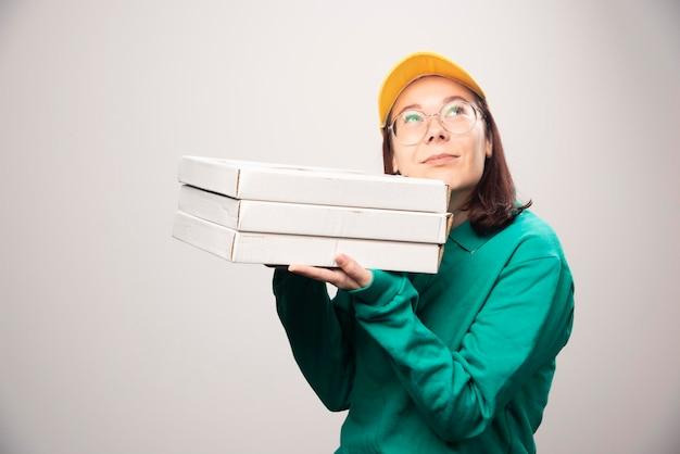 Entregadora carregando cartolinas de pizza em um branco. foto de alta qualidade