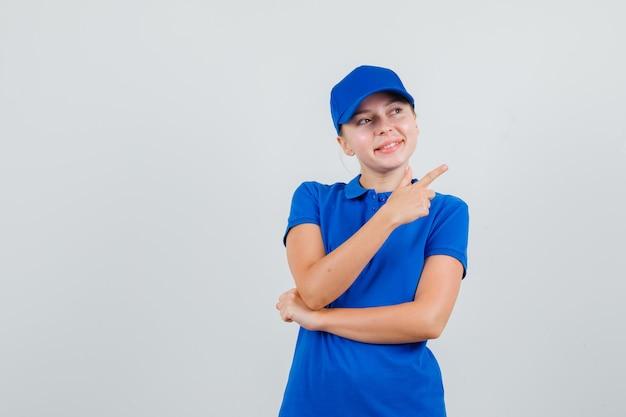 Entregadora com camiseta azul e boné apontando para o lado e parecendo alegre