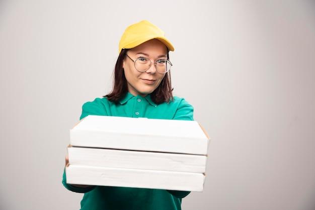 Entregadora dando cartolinas de pizza em um branco. foto de alta qualidade
