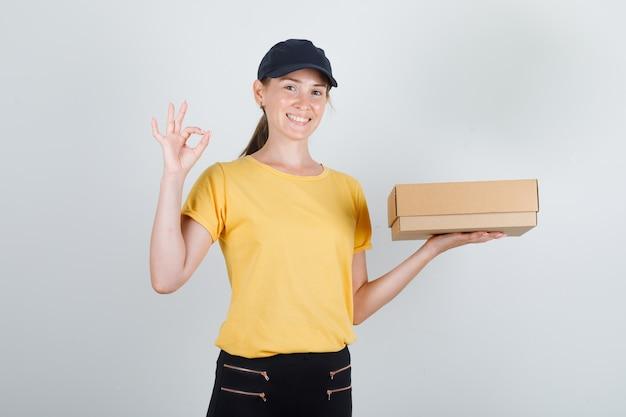 Entregadora de camiseta, calça e boné segurando uma caixa de papelão com o sinal de ok e parecendo satisfeita