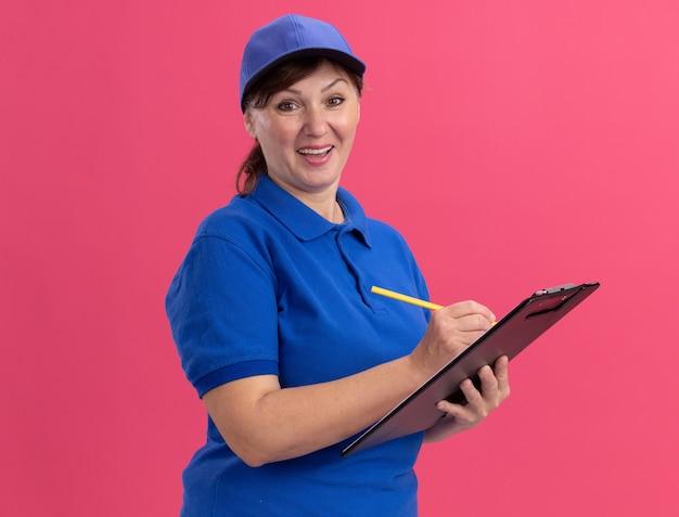 Entregadora de meia-idade com uniforme azul e boné segurando a prancheta e escrevendo a lápis olhando para a frente hapy e positiva sorrindo alegremente em pé sobre a parede rosa