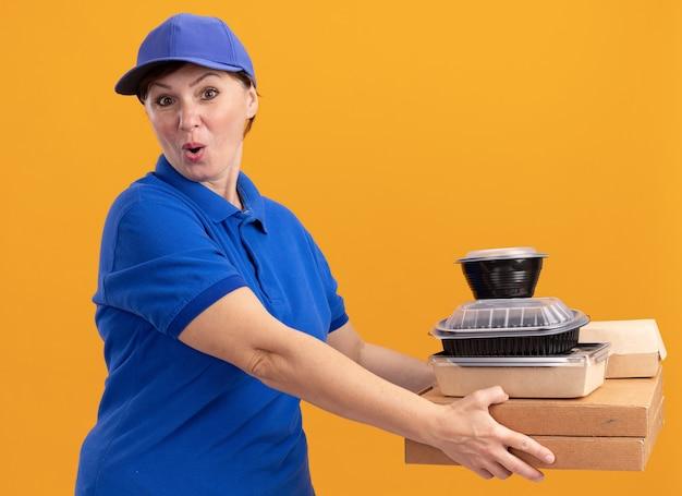 Entregadora de meia-idade com uniforme azul e boné segurando caixas de pizza e pacotes de comida olhando para a frente feliz e surpresa em pé sobre a parede laranja