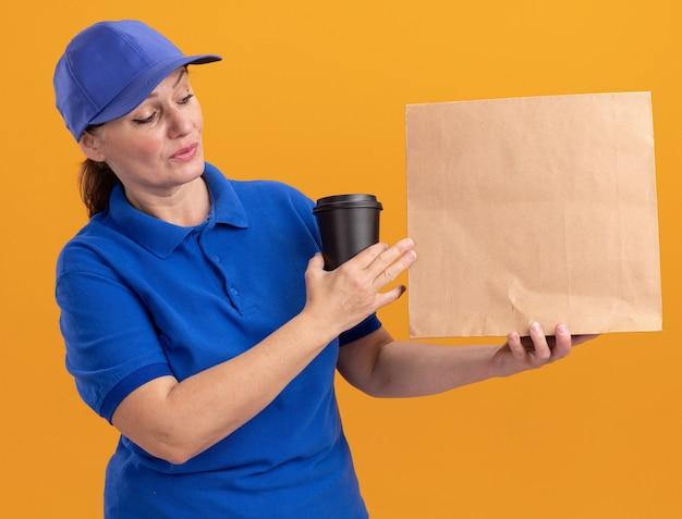 Entregadora de meia-idade com uniforme azul e boné segurando um pacote de papel e uma xícara de café, olhando com uma cara séria em pé sobre uma parede laranja