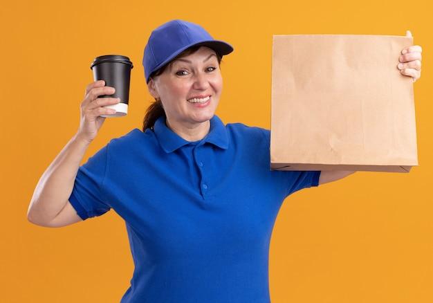 Entregadora de meia-idade com uniforme azul e boné segurando um pacote de papel mostrando a xícara de café olhando para frente sorrindo alegremente em pé sobre a parede laranja