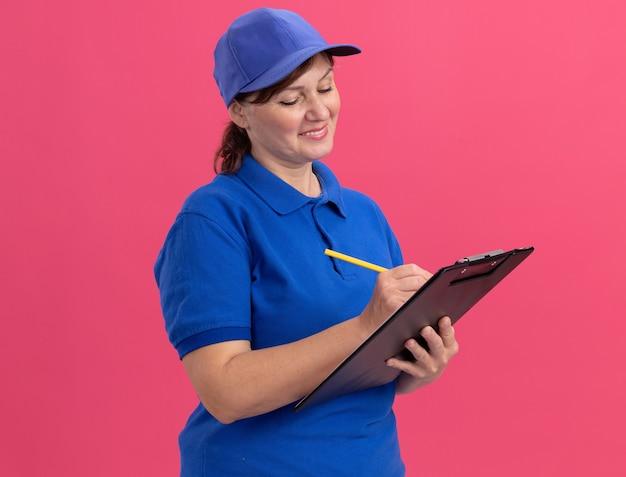 Entregadora de meia-idade com uniforme azul e boné segurando uma prancheta e escrevendo a lápis com um sorriso no rosto em pé sobre a parede rosa