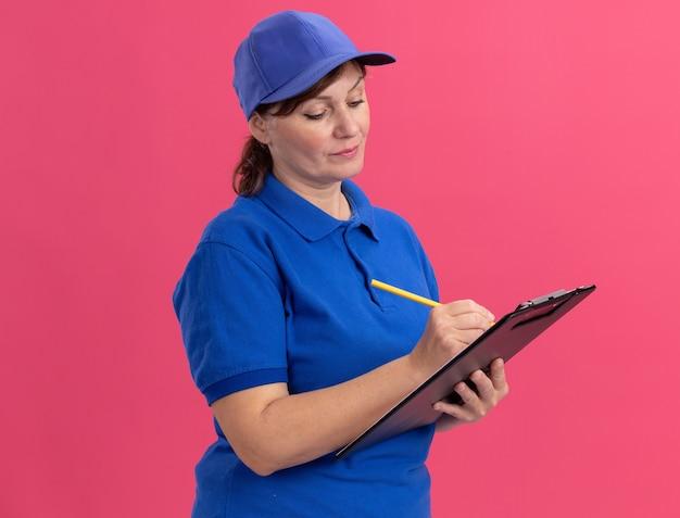 Entregadora de meia-idade com uniforme azul e boné segurando uma prancheta e escrevendo a lápis com uma cara séria em pé sobre a parede rosa