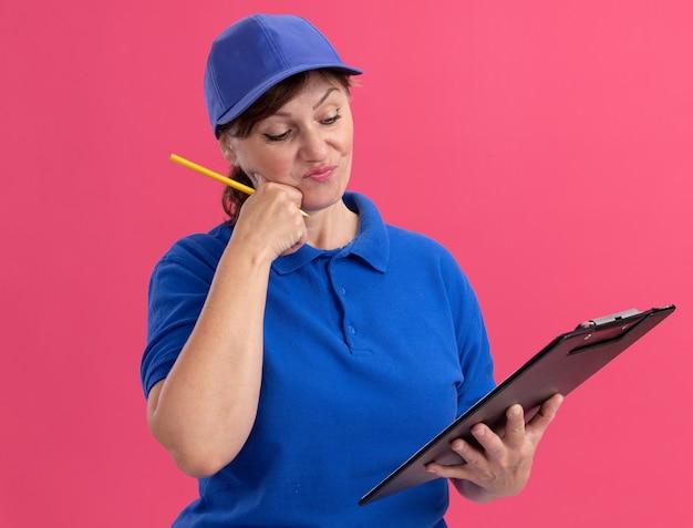 Entregadora de meia-idade com uniforme azul e boné segurando uma prancheta e um lápis olhando para ela com uma expressão confusa em pé sobre a parede rosa