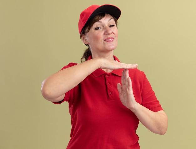 Entregadora de meia-idade com uniforme vermelho e boné olhando para a frente, sorrindo, fazendo um gesto de pausa com as mãos em pé sobre a parede verde