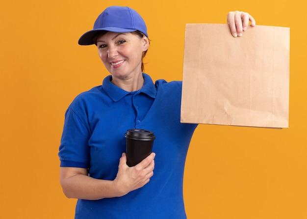 Entregadora de meia-idade feliz com uniforme azul e boné mostrando um pacote de papel segurando uma xícara de café, olhando para a frente, sorrindo em pé sobre a parede laranja