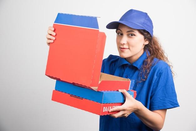 Entregadora de pizza abrindo uma das caixas de pizza no fundo branco