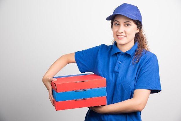 Entregadora de pizza carregando três caixas em fundo branco