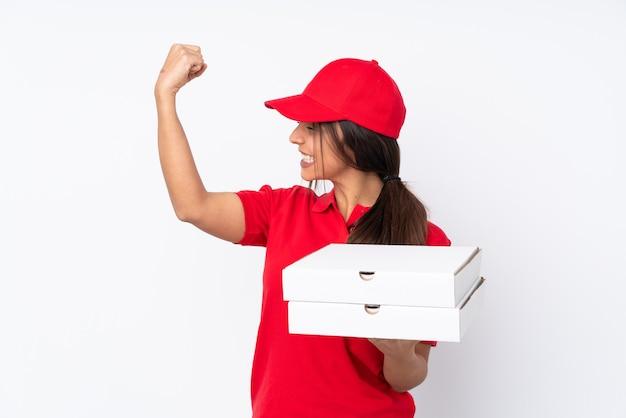 Entregadora de pizza jovem em fundo branco isolado comemorando vitória