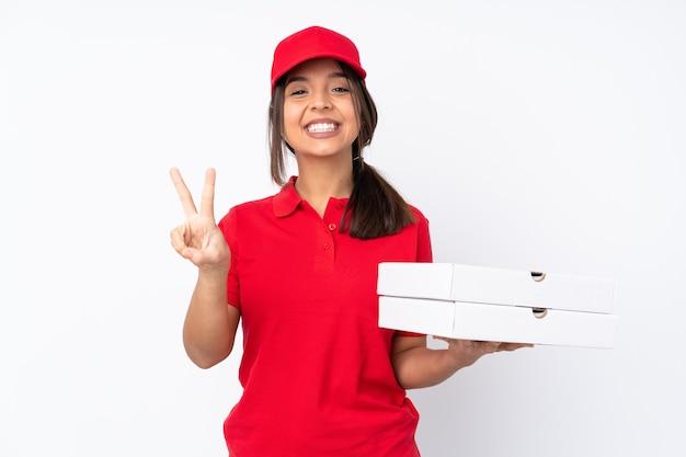 Entregadora de pizza jovem em fundo branco isolado sorrindo e mostrando sinal de vitória