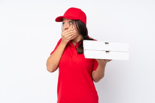 Entregadora de pizza jovem sobre fundo branco isolado cobrindo a boca e olhando para o lado