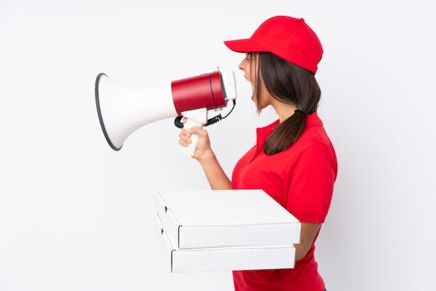 Entregadora de pizza jovem sobre parede branca isolada, gritando através de um megafone