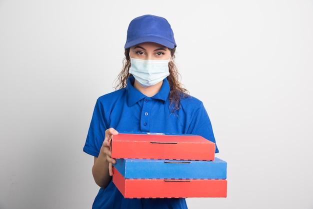 Entregadora de pizza segurando três caixas com máscara médica em branco