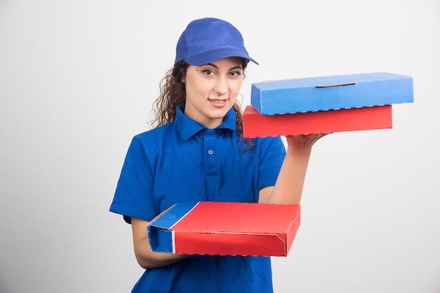 Entregadora de pizza segurando três caixas em fundo branco. foto de alta qualidade