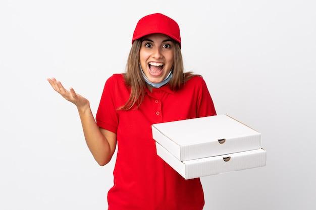Entregadora de pizza segurando uma pizza e se protegendo do coronavírus com uma máscara na parede branca isolada com expressão facial chocada