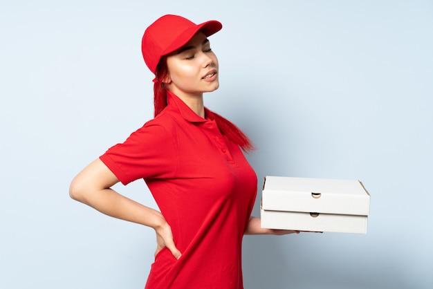 Entregadora de pizza, segurando uma pizza na parede, sofrendo de dor nas costas por ter feito um esforço