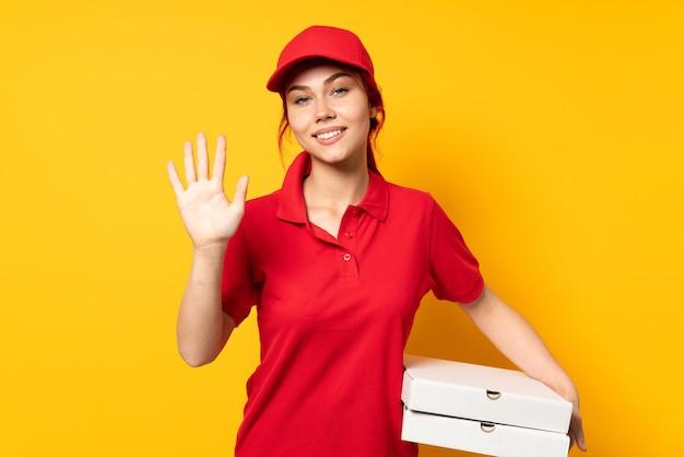 Entregadora de pizza segurando uma pizza sobre um fundo isolado, contando cinco com os dedos