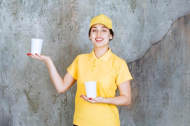 Entregadora de uniforme amarelo segurando dois copos plásticos de bebida e dando um para a outra pessoa.