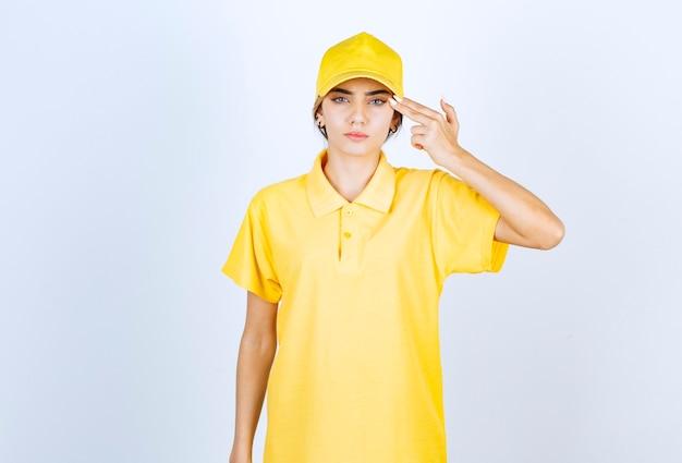 Entregadora de uniforme amarelo segurando dois dedos perto da têmpora, como uma pistola.