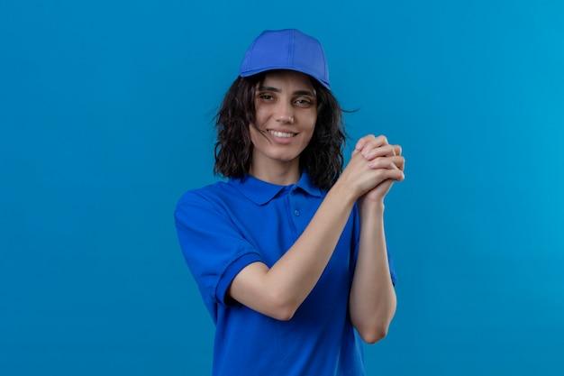 Entregadora de uniforme azul e boné em pé com um gesto de trabalho em equipe, sorrindo amigavelmente no azul isolado