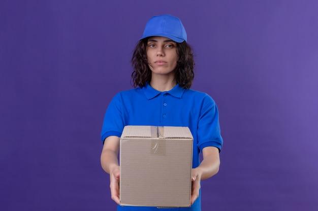 Entregadora de uniforme azul e boné esticando a embalagem da caixa com expressão séria e confiante em pé no roxo isolado