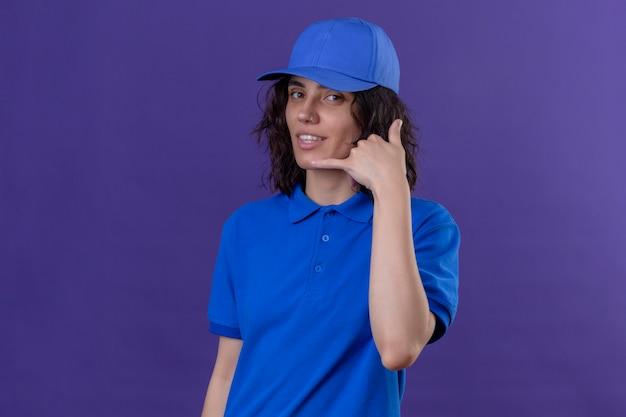 Entregadora de uniforme azul e boné fazendo um gesto de me chamar de sorriso amigável no roxo isolado