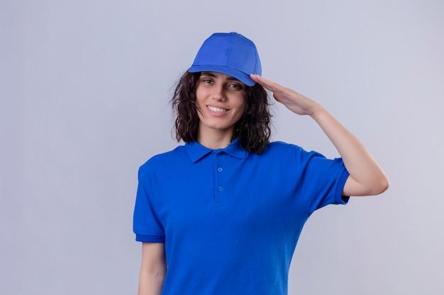 Entregadora de uniforme azul e boné saudando sorrindo amigavelmente em branco isolado