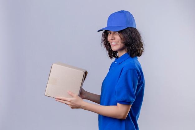 Entregadora de uniforme azul e boné segurando a embalagem da caixa de pé de lado, parecendo confiante em branco isolado