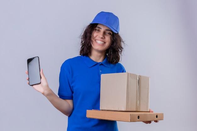 Entregadora de uniforme azul e boné segurando caixas de pizza e embalagem mostrando o celular sorrindo alegremente em pé no branco