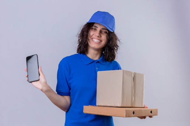 Entregadora de uniforme azul e boné segurando caixas de pizza e embalagem mostrando o celular sorrindo alegremente em pé