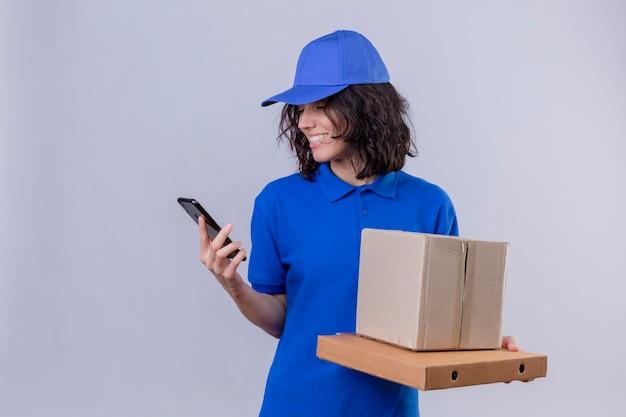 Entregadora de uniforme azul e boné segurando caixas de pizza e pacote de caixa olhando para a tela do celular sorrindo com o rosto feliz em pé