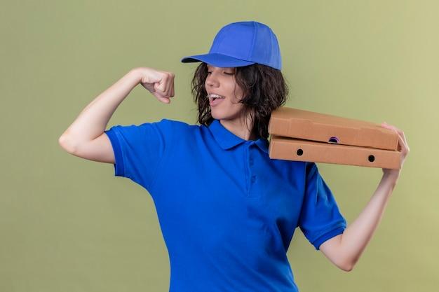 Entregadora de uniforme azul e boné segurando caixas de pizza mostrando bíceps sorrindo alegremente em pé sobre um espaço verde isolado