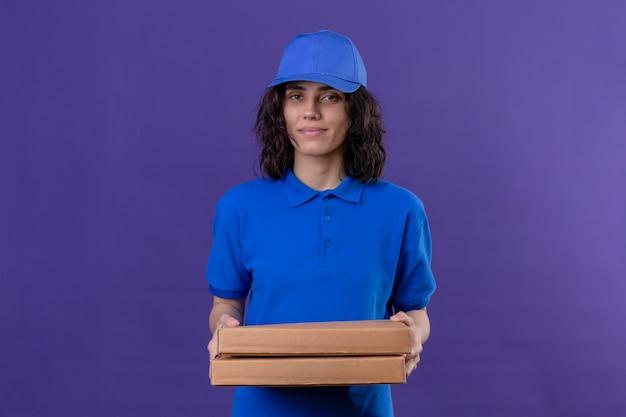 Entregadora de uniforme azul e boné segurando caixas de pizza sorrindo confiante em pé no roxo