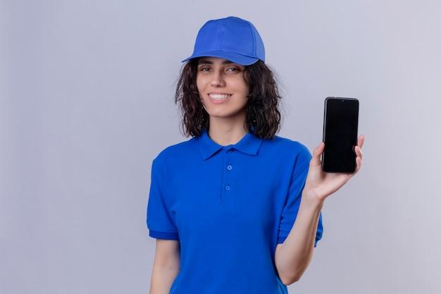 Entregadora de uniforme azul e boné segurando e mostrando o celular parecendo positiva e feliz sorrindo em pé sobre branco