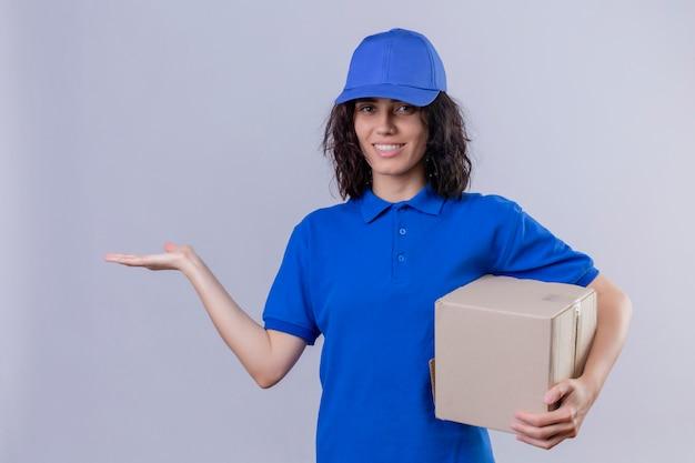 Entregadora de uniforme azul e boné segurando um pacote de caixa apresentando-se com o braço da mão sorrindo alegremente em pé no branco
