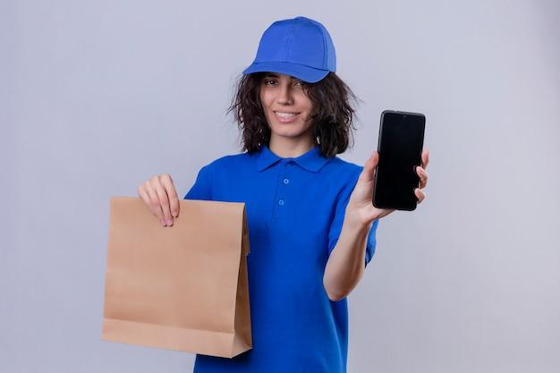 Entregadora de uniforme azul e boné segurando um pacote de papel mostrando o celular sorrindo alegremente em pé no branco