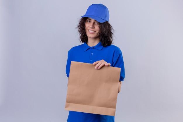 Entregadora de uniforme azul e boné segurando um pacote de papel, sorrindo, alegre, com um rosto feliz em pé no branco
