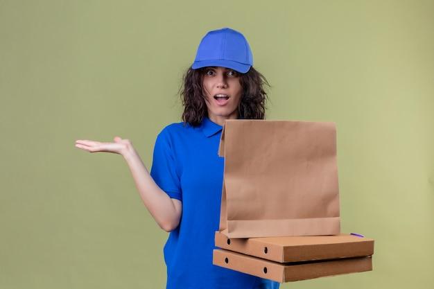 Entregadora de uniforme azul segurando caixas de pizza e um pacote de papel parecendo incerta e confusa, sem resposta, espalhando as palmas das mãos em pé sobre o espaço verde oliva