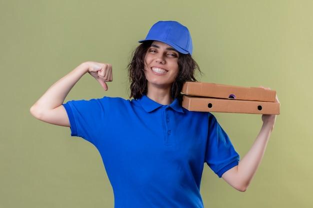 Entregadora de uniforme azul segurando caixas de pizza mostrando bíceps sorrindo alegremente em pé sobre um espaço verde isolado