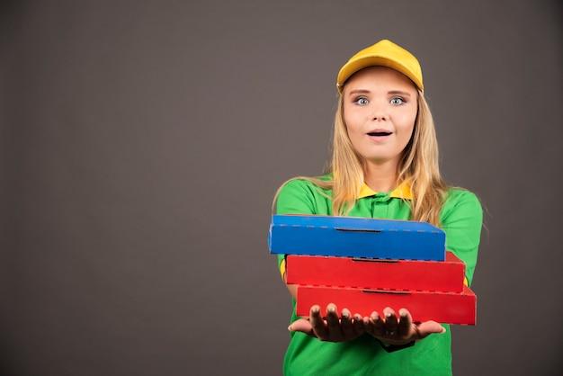Entregadora de uniforme dando cartolinas de pizza.