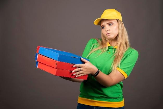 Entregadora de uniforme segurando cartolinas de pizza. foto de alta qualidade