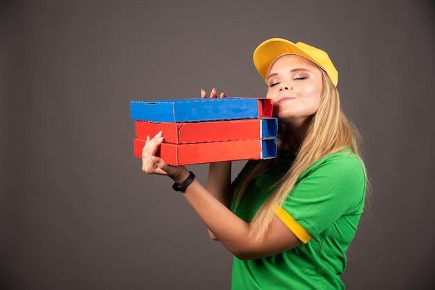 Entregadora de uniforme segurando cartolinas de pizza.
