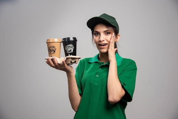 Entregadora de uniforme verde em pé com xícaras de café.