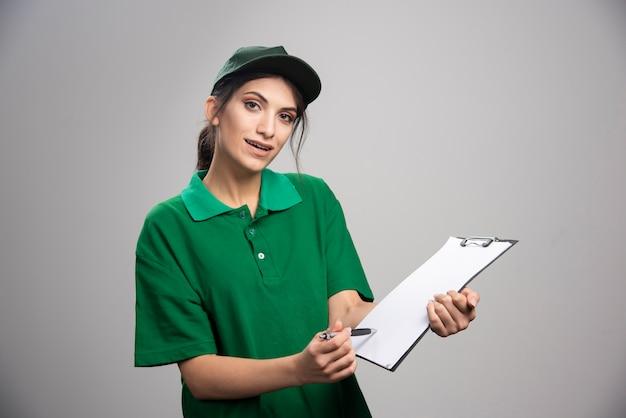 Entregadora de uniforme verde mostra onde assinar.